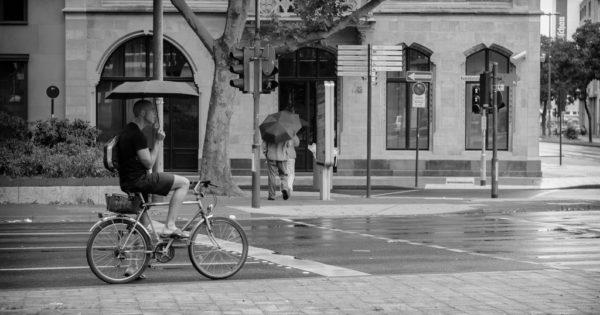 Man cycling in the rain.