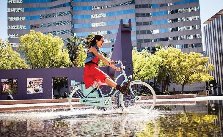 Woman Riding Bike Through Water